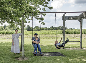 The Martins, a Mennonite family, gather around their swing set in the backyard of their Memphis, Missouri home