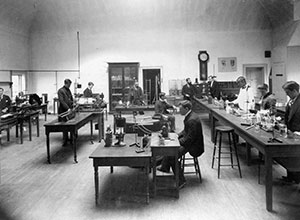 In the early 1900s, U-M students studied physiology in the department's laboratory in the C.C. Little Building on the main campus. Warren P. Lombard, M.D., is the bearded man to the left of the wall clock.