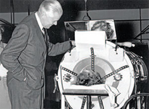 U-M President Harlan Hatcher visits a polio patient in an iron lung (ca. 1954)
