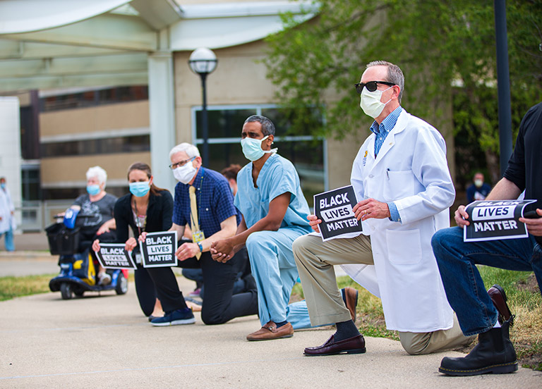 Doctors and hospital staff kneeling and holding black lives matter signs in front of building.