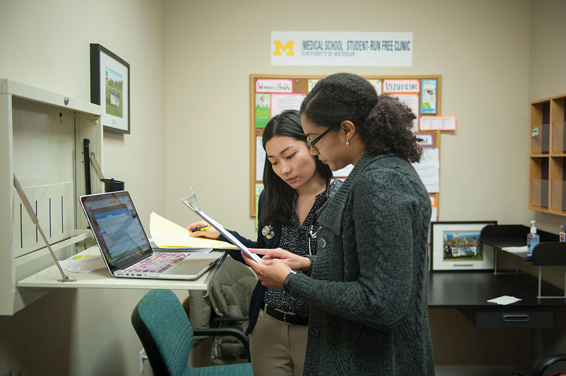Michelle Ng, a first-year medical student, reviews patient information with Angelica Willis (M.D. 2018), MPH.