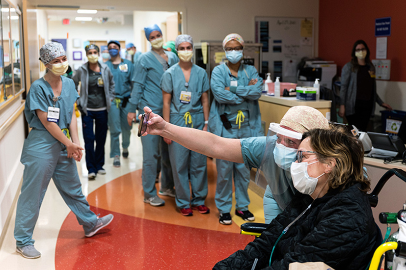 Fellow nurses and other health care providers celebrate their colleague Michelle Davis's discharge from the hospital after being treated for COVID-19.