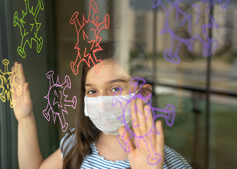 Girl wearing mask behind glass with coronavirus drawings