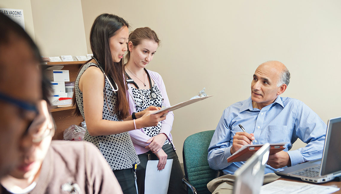 Two medical students discuss a patient visit with Rafat Rizk, M.D., assistant professor of gastroenterology, at the U-M Student-Run Free Clinic.