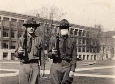 Two soldiers on campus on Armistice Day, November 11, 1918. One is wearing a mask due to the flu pandemic.